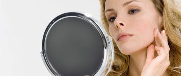 Young woman looking in mirror, touching face